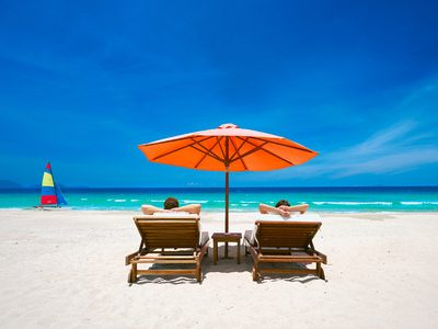 44178180-couple-on-a-tropical-beach-relax-in-the-sun-on-deck-chairs-under-a-red-umbrella-travel-background-