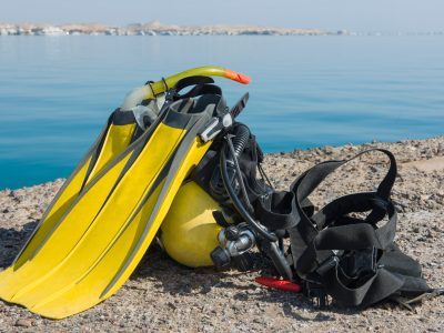 Full set of scuba diving equipment on the ground next to a tropical sea coast